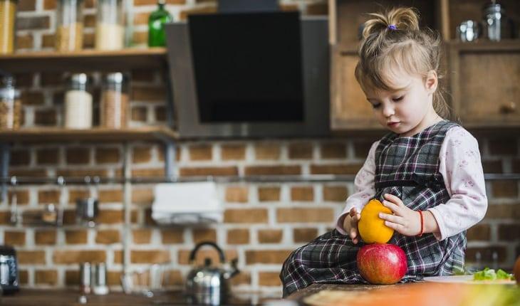 Alimentação vegana na gravidez: na foto, uma criança sentada em uma bancada de cozinha mexendo e olhando para duas frutas.