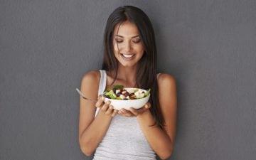A foto mostra uma mulher segurando uma tigela de salada, ilustrando o post sobre alimentos para perder peso