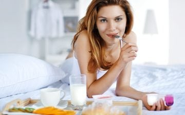 Mulher tomando café da manhã, uma das dicas para acelerar o metabolismo