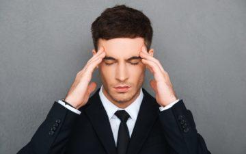 Alimentos para a memória. Na foto, um homem de terno preocupado com memória coloca as mãos na cabeça
