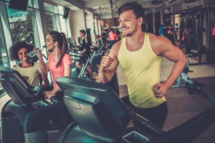 A foto mostra um homem com uma regata amarela correndo na esteira em uma academia e sorrindo. Ao seu lado está uma mulher com camiseta rosa caminhando, bebendo água e conversando com sua treinadora