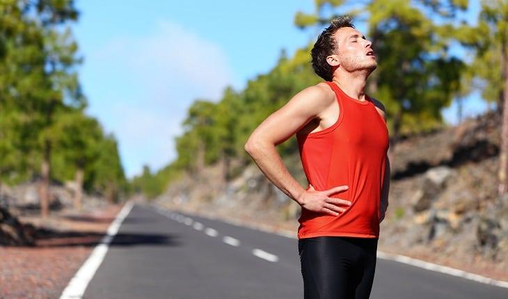 A foto mostra um homem descansando após uma corrida na estrada