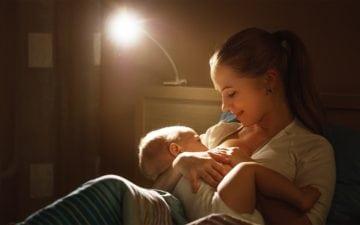 Alimentação da mãe durante a amamentação: dicas e cuidados. Na foto, uma mulher sentada em um ambiente pouco iluminado amamentando um bebê