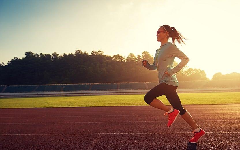 A foto mostra uma mulher correndo em uma pista enquanto o sol se põe. A imagem ilustra o tema do post sobre dicas para correr mais