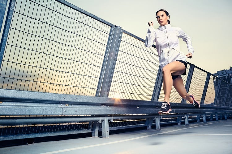 A foto mostra uma mulher correndo muito rápido. A foto foi tirada no momento em que ela está com os dois pés fora do chão