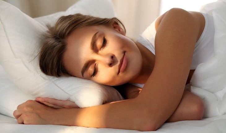 A foto mostra uma mulher dormindo em sua cama com uma expressão tranquila
