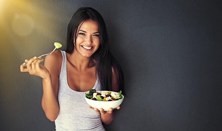 A foto mostra uma mulher sorrindo comendo uma refeição equilibrada com muita salada