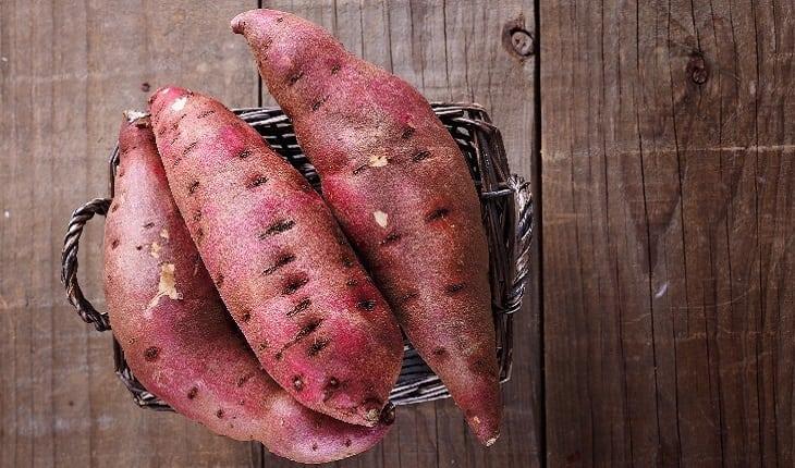 A foto mostra uma cesta com três batatas-doces, um dos alimentos para corredores