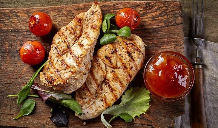 A foto mostra dois filés de frangos grelhados acompanhados de vegetais e tomates, um dos alimentos para corredores