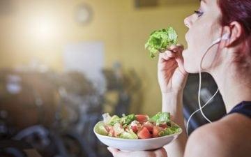 A foto mostra uma mulher com fone de ouvido comendo salada em uma academia. A foto ilustra o tema do post sobre indicações de alimentos para corredores