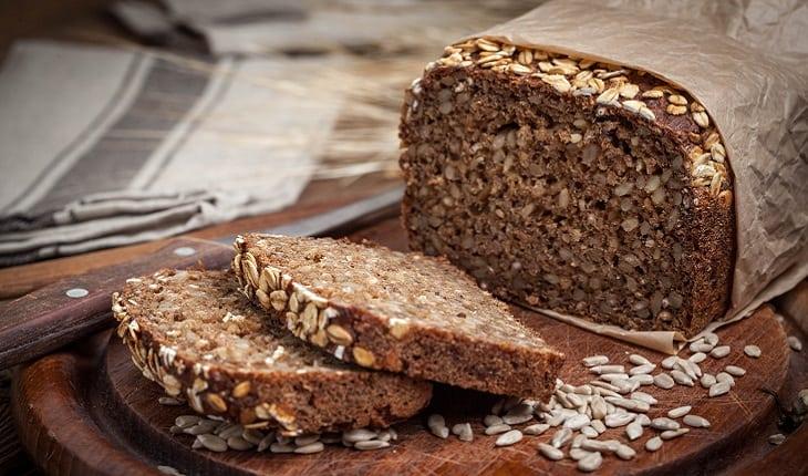 A foto mostra um pão integral fatiado, um dos alimentos para corredores