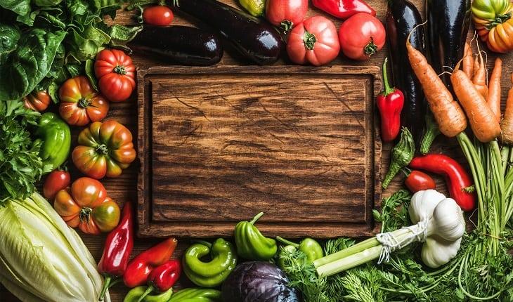 A foto mostra vegetais e legumes variados ao redor de uma tábua de madeira. Esses são indicações de alimentos para corredores