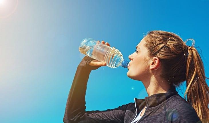 Mulher bebendo água, seguindo os conselhos de especialistas, hidrate-se