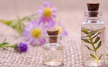 A foto mostra dois frascos, um grande e um pequeno com óleos aromáticos e flores ao fundo, ilustrando o tema do post sobre os benefícios da aromaterapia