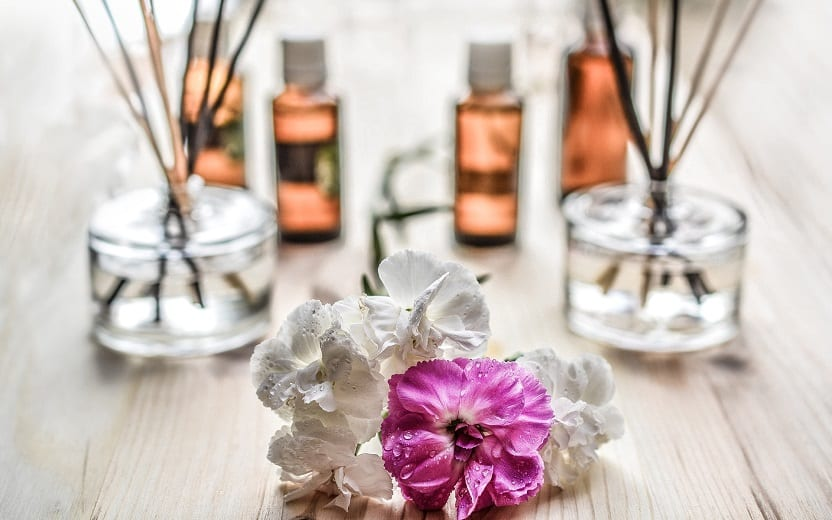 A foto mostra 4 frascos com óleos aromáticos desfocados ao fundo e flores brancas e rosas em foco na frente. A imagem ilustra o tema do post sobre os benefícios da aromaterapia