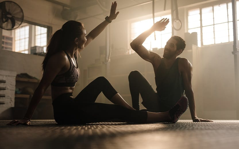 A foto mostra um homem e uma mulher sentados em uma academia sorrindo e se cumprimentando após treinarem. A imagem ilustra o tema do post sobre os benefícios de se treinar com amigos