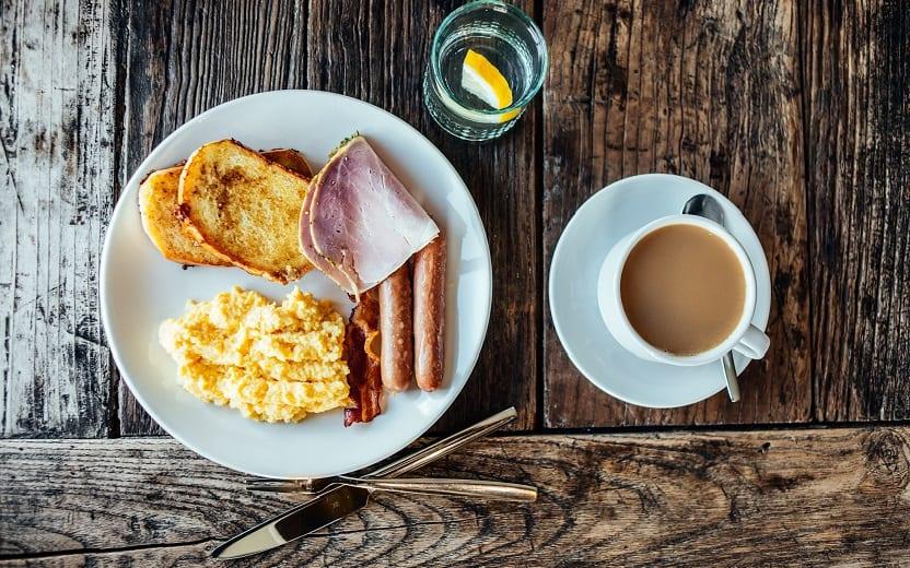 Prato repleto de alimentos característicos, contendo a primeira refeição do dia, café da manhã, em cima da mesa