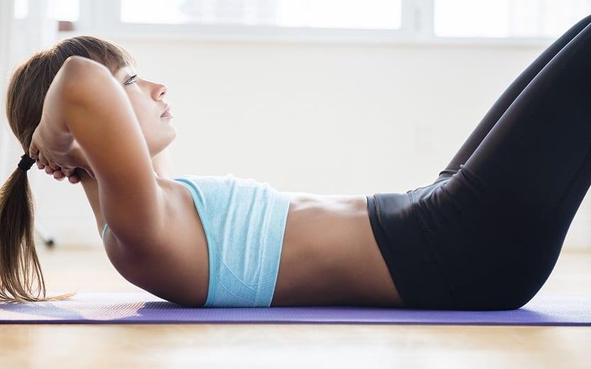 A foto mostra uma mulher deitada no chão apoiando a cabeça, suspensa no ar, com as mãos e fazendo uma super série funcional de abdominais