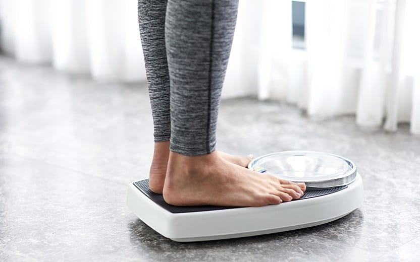A foto mostra uma mulher em cima de uma balança descalça. A imagem ilustra o tema do post sobre como chegar ao peso ideal