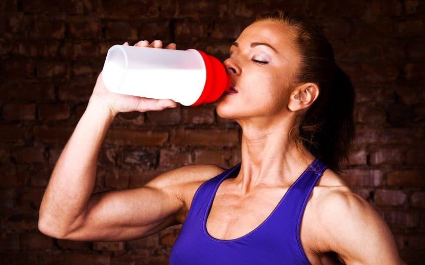 A foto mostra uma mulher tomando seu suplemento em uma coqueteleira. A imagem ilustra uma das dicas sobre como chegar ao peso ideal