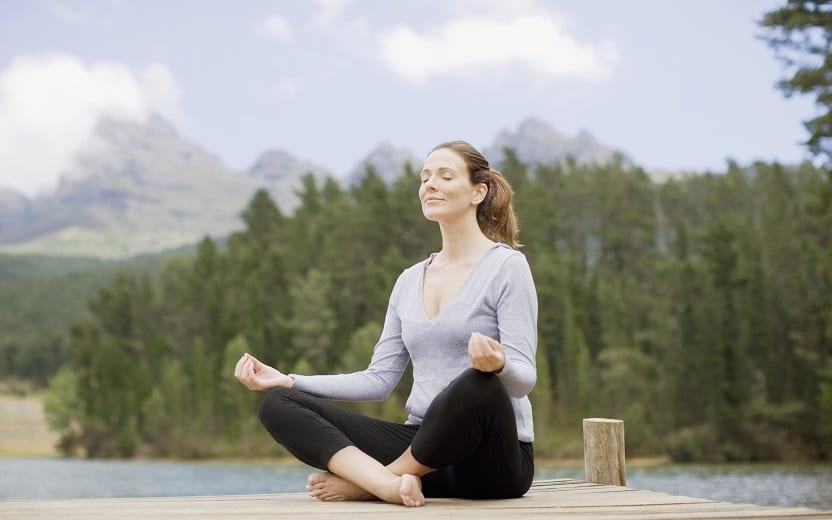 Mulher sentada, meditando, em um cais na beira de um rio conhece 5 benefícios da prática para a mente e corpo humano