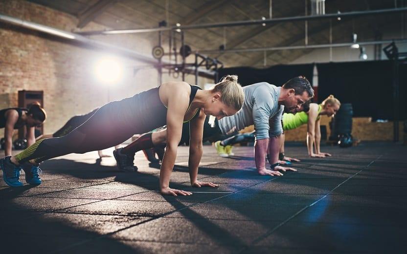 Pessoas fazendo flexões e buscando desenvolver o condicionamento físico, enquanto pensam nos 5 erros que sabotam os resultados físicos