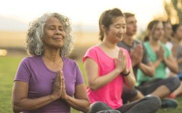 Mulheres sentadas em um campo com mãos cruzadas, praticando meditação conhece 5 benefícios da meditação para a mente e o corpo humano