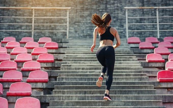 Mulher subindo escadas, refletindo sobre os 5 erros que sabotam o condicionamento físico
