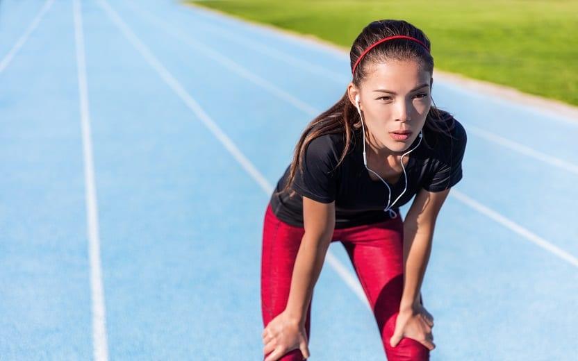 A foto mostra uma mulher em uma pista de corrida azul se apoiando em seus joelhos demonstrando sentir cansaço