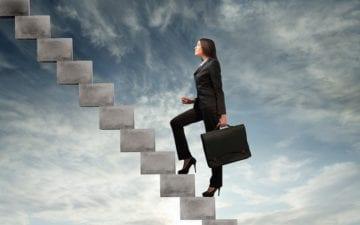 A foto mostra uma mulher subindo uma escada com uma maleta em mãos e vestindo um terno preto. A imagem ilustra o tema do post sobre como os exercícios físicos podem melhorar o desempenho no trabalho. Ao fundo, está um céu nublado