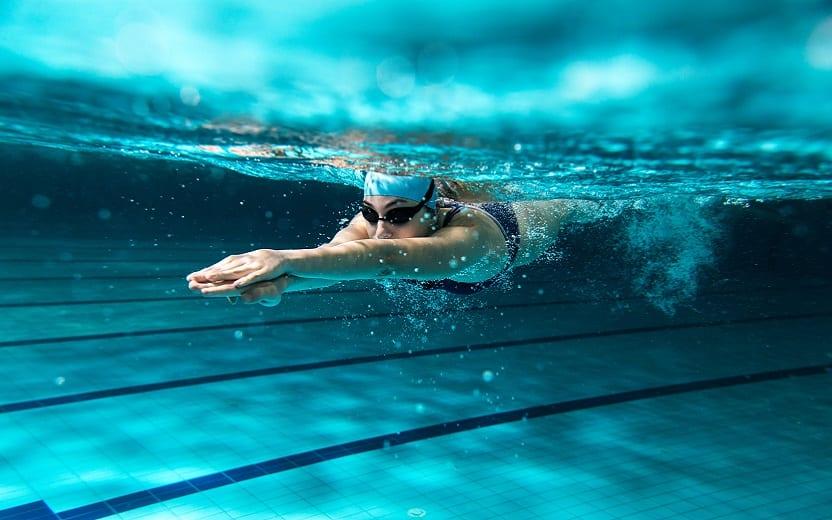 A foto mostra uma mulher nadando, com os braços esticados, totalmente submersa em uma piscina. A natação é um dos exercícios indicados para melhorar o desempenho no trabalho