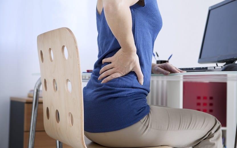 A foto mostra uma mulher sentada em frente a um computador com a mão em suas costas, mostrando que está com dor no local. Sentar torto é um dos hábitos posturais que prejudicam a coluna