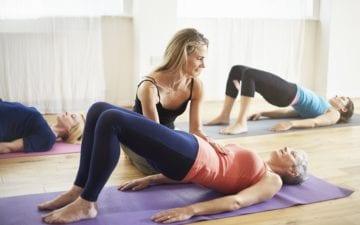 Instrutora de pilates levanta a região lombar de uma mulher , a auxiliando a ter maior controle sobre a respiração e ensinando os principais conceitos do pilates