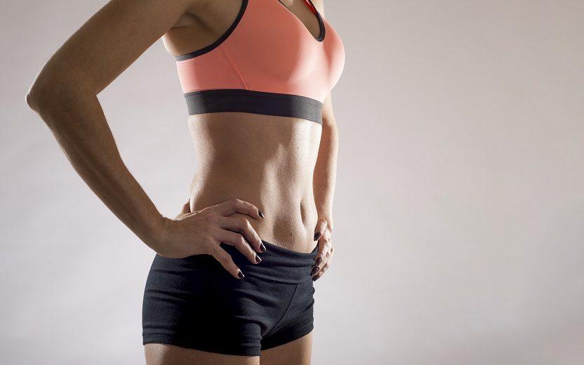 Exercícios funcionais para definir o abdômen. Na foto, uma mulher com roupa de academia e o abdômen definido