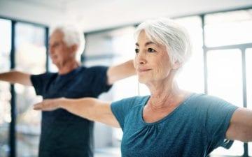 A foto mostra um casal de idosos, uma senhora em foco na frente e um senhor desfocado ao fundo, sorrindo e praticando atividade física, ilustrando o tema do post sobre exercícios que aumentam a expectativa de vida