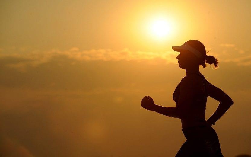 Silhueta de uma mulher correndo durante o dia. Benefícios do exercício contra o câncer