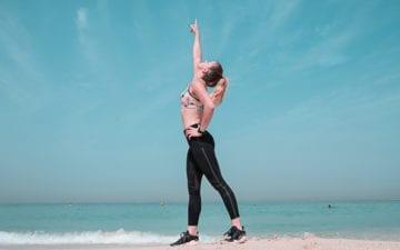 Mulher praticando seus exercícios dos treinos de verão na praia