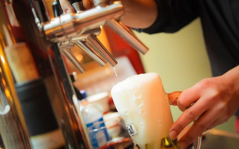 Homem servindo em um copo de cerveja