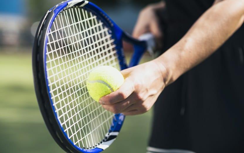 A foto mostra um homem segurando uma raquete e uma bola de tênis, um dos exercícios que aumentam a expectativa de vida
