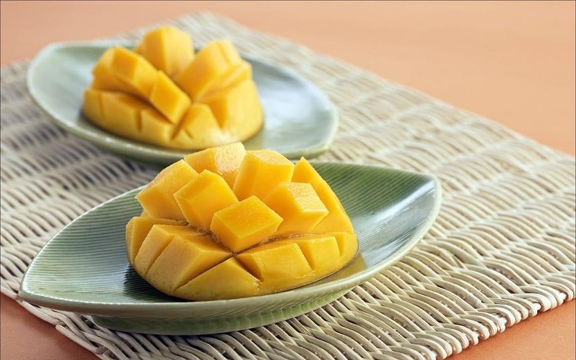 A foto mostra duas mangas descascadas e picadas. Essa fruta é um dos alimentos que auxiliam na proteção solar