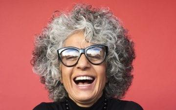 A foto mostra uma mulher idosa de óculos e com uma blusa preta sorrindo. A imagem ilustra o tema do post sobre alimentação na terceira idade contra a depressão