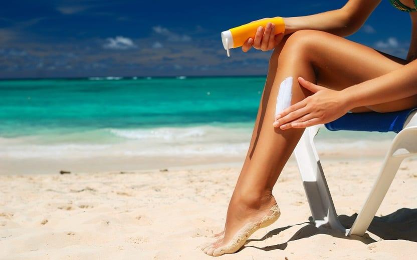 A foto mostra uma mulher sentada na praia passando protetor em sua perna. A imagem ressalta a importância da proteção sola