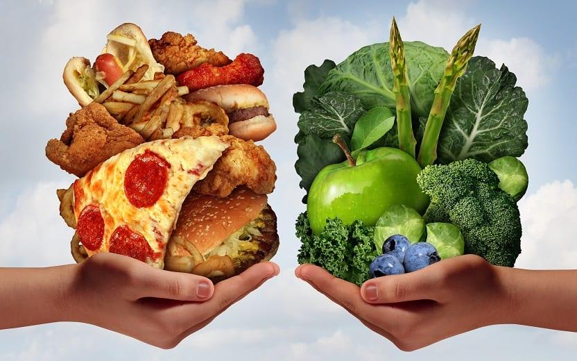 Duas mãos seguram alimentos saudáveis e alimentos que podem prejudicar a saúde