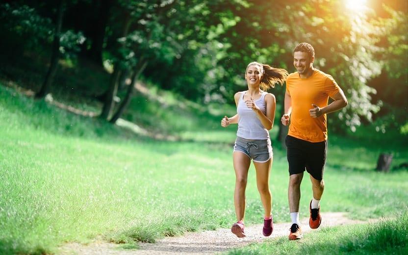 Casal corre em trilha em meio a floresta. Realizar atividade física é uma das dicas para queimar mais calorias