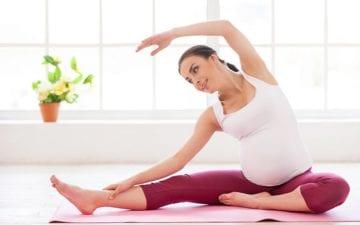 A foto mostra uma mulher grávida sentada descalça e com roupas de ginástica alongando. Ela está sorrindo, ilustrando os benefícios dos exercícios físicos para gestantes