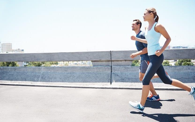 Uma mulher e um homem correm um do lado do outro em uma rua. Eles estão aprendendo os diferentes treinos de corrida