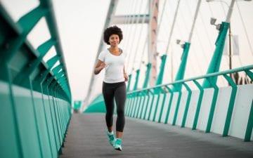 Mulher correndo em uma passarela verde, aprende sobre os diferentes treinos de corrida