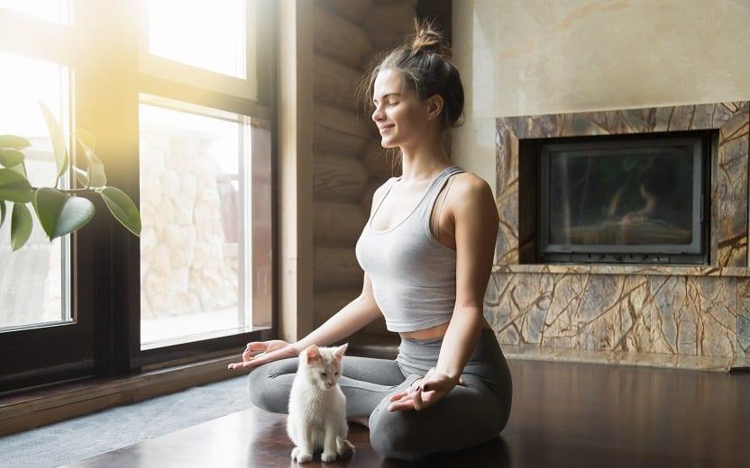 Mulher sentada em uma sala relaxante aprenda a meditar em um passo a passo