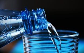 Dicas para evitar pedras nos rins: beber água. Na imagem, uma garrafa enchendo copo de água.