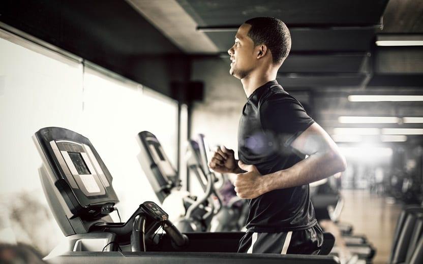Homem realiza exercício físico na academia, correndo na esteira. Dicas para ficar em forma